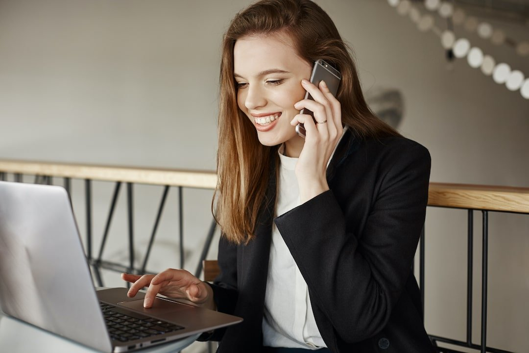 Successful businesswoman smiling as talking on phone and working with laptop in cafe.