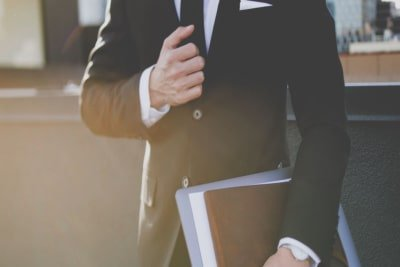 Man in suit holding leather folder on way to business meeting.