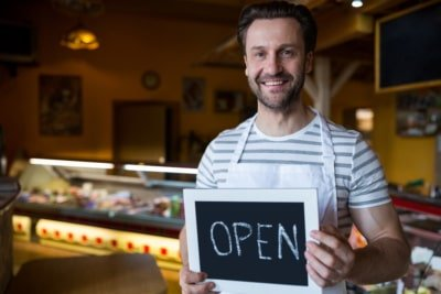 Smiling small business owner holding a open sign in the bakery shop.
