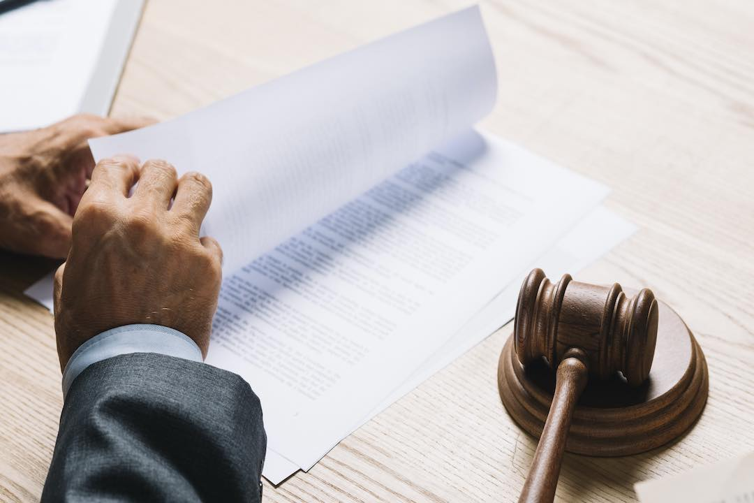 Male lawyer reviewing bankruptcy documents in a courtroom.