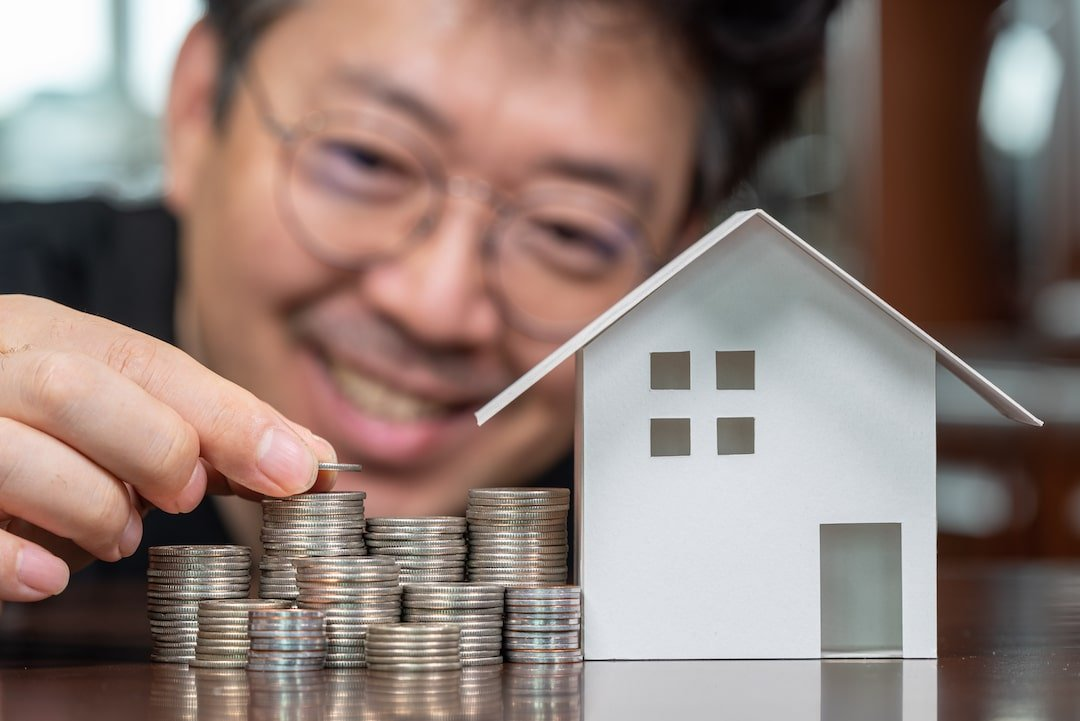 Asian man stacking coins next to model house for home equity loan concept.