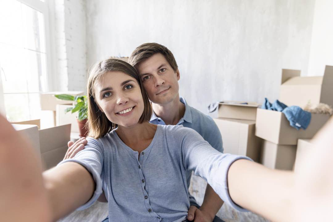 Smiley couple taking a selfie while unpacking in their new home.
