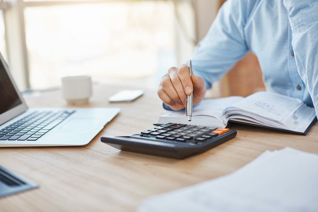 Equipment lessor using calculator to calculate profit from using credit repair with his customers.