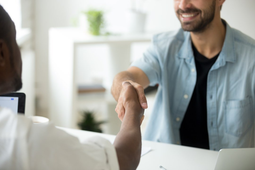 Male mortgage broker shaking hands with client with bad credit after mortgage loan close.