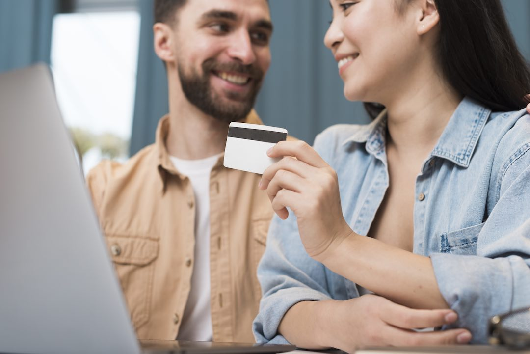 Happy couple after bankruptcy using new credit card.