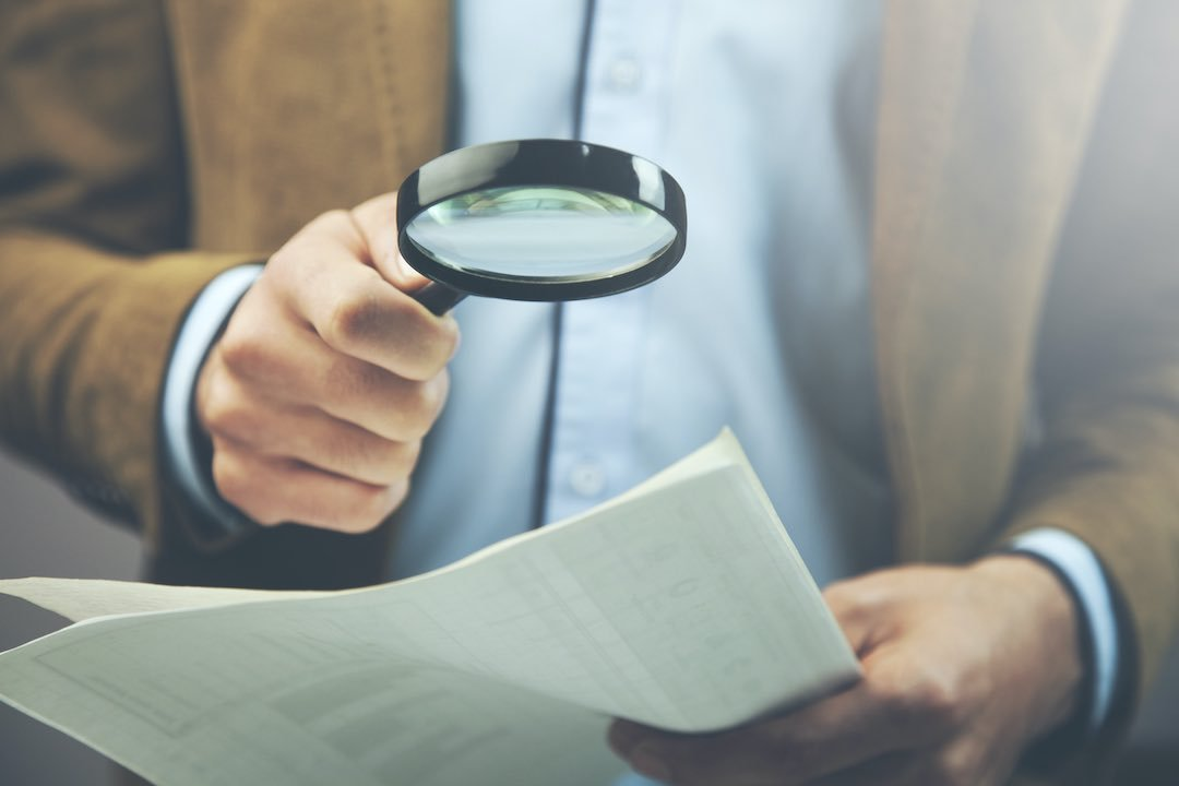 Man experiencing bankruptcy scanning credit bureau report with magnifying glass.
