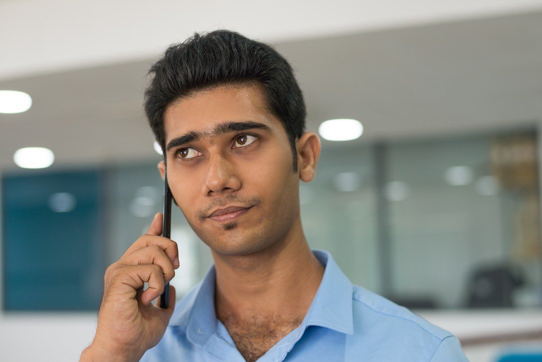 Pensive Indian man listening to bill collector on mobile phone.