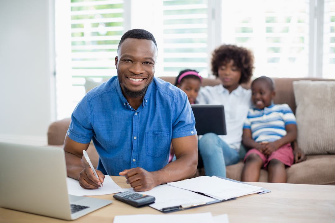 Man in blue shirt with smile from successful collections negotiation methods with family on couch behind him.