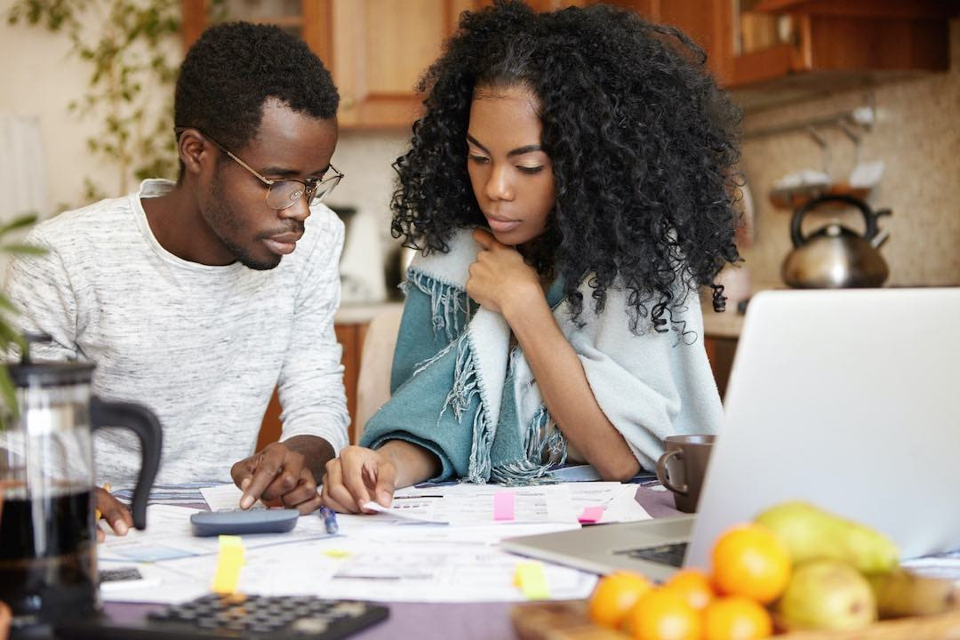 Indoor candid shot of young african-american couple doing paperwork together.