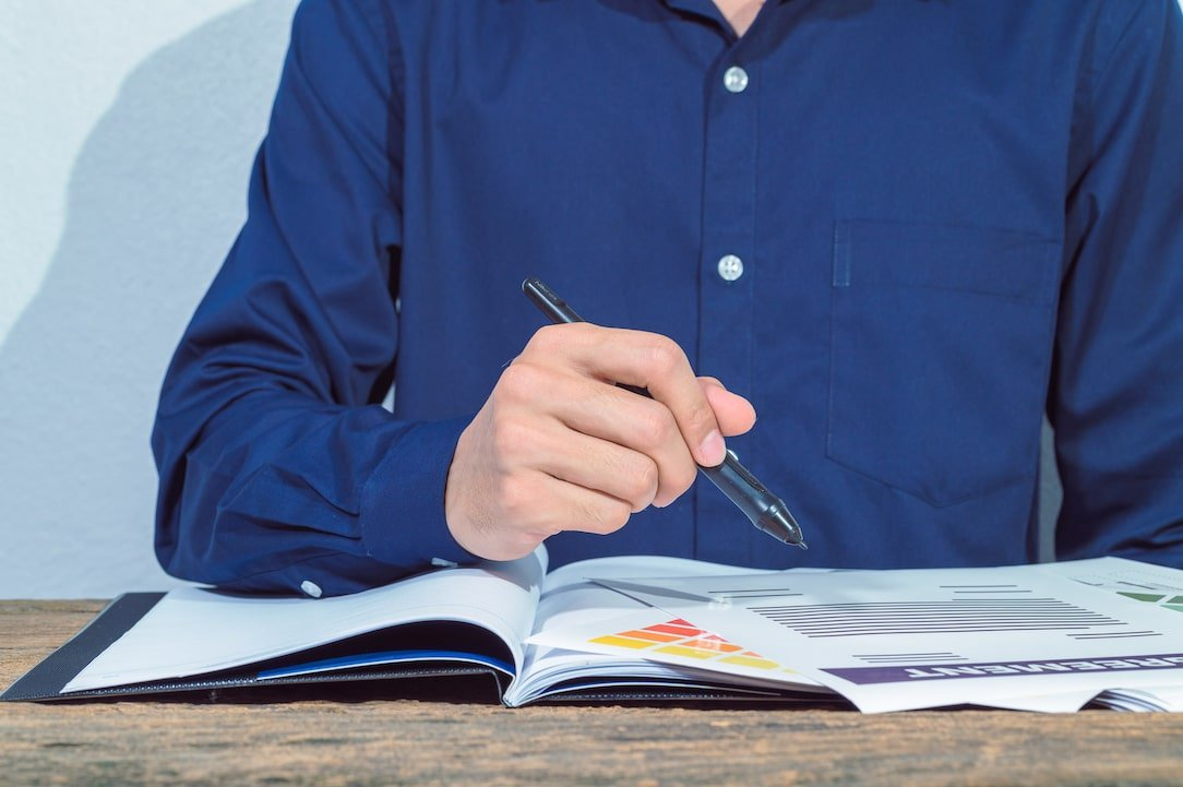 Man in blue shirt checks his credit report on the table.