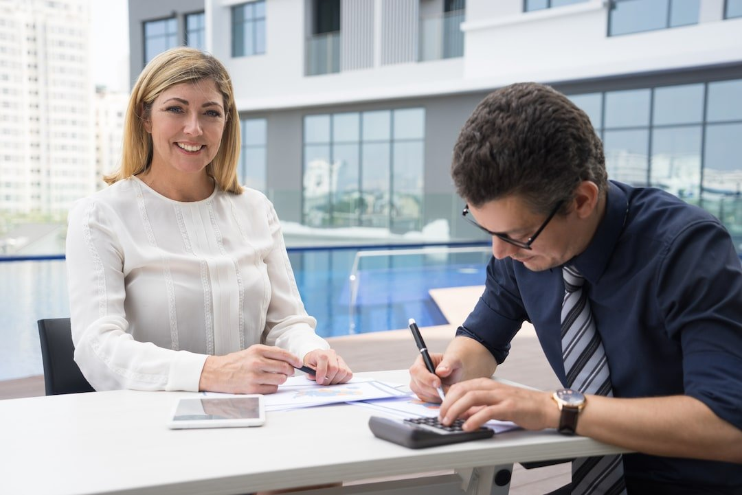 Cheerful excited mature female financier smiling while loan officer using calculator.