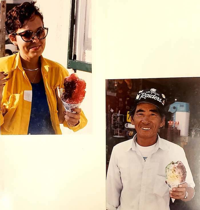Smiling African American woman and Asian man holding shaved ice cones.