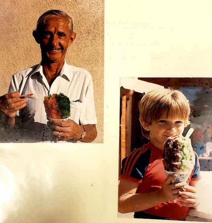 Smiling older man and young child holding shaved ice cones.